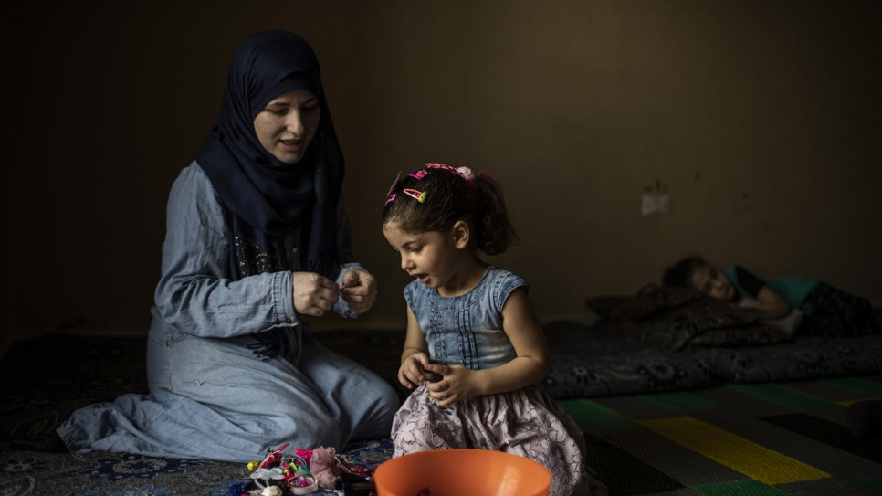 Syrian refugee Wafaa pins daughter Yasmine's hair at their home in Barja, Lebanon.