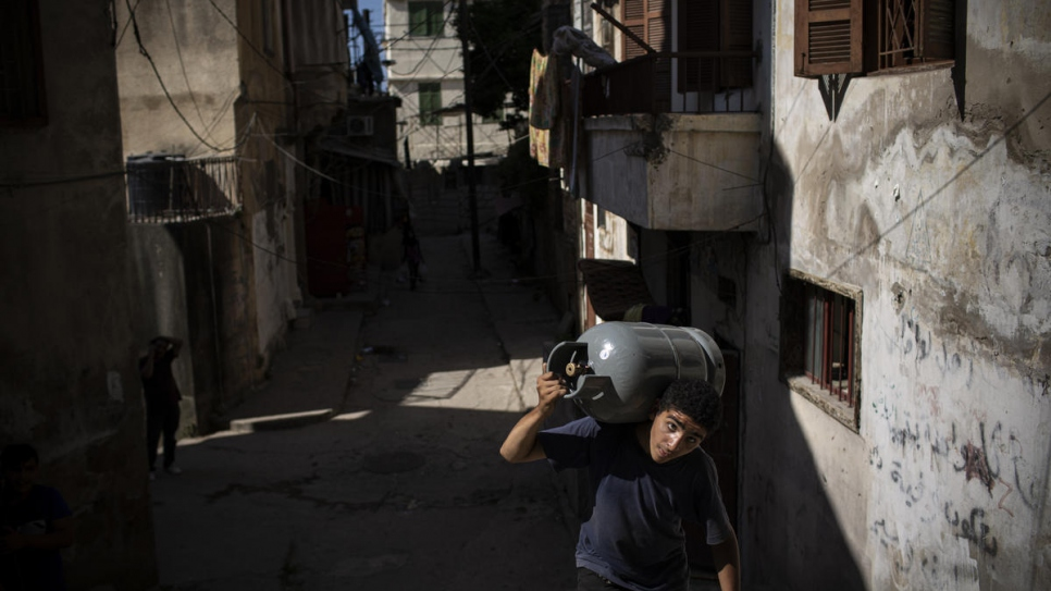 A young Syrian refugee carries a gas canister through Bab al-Tabbaneh neighbourhood in Tripoli, Lebanon.