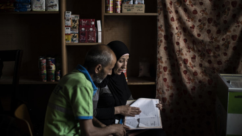 Kawkab and her husband Rabie check the ledgers of her struggling convenience store.