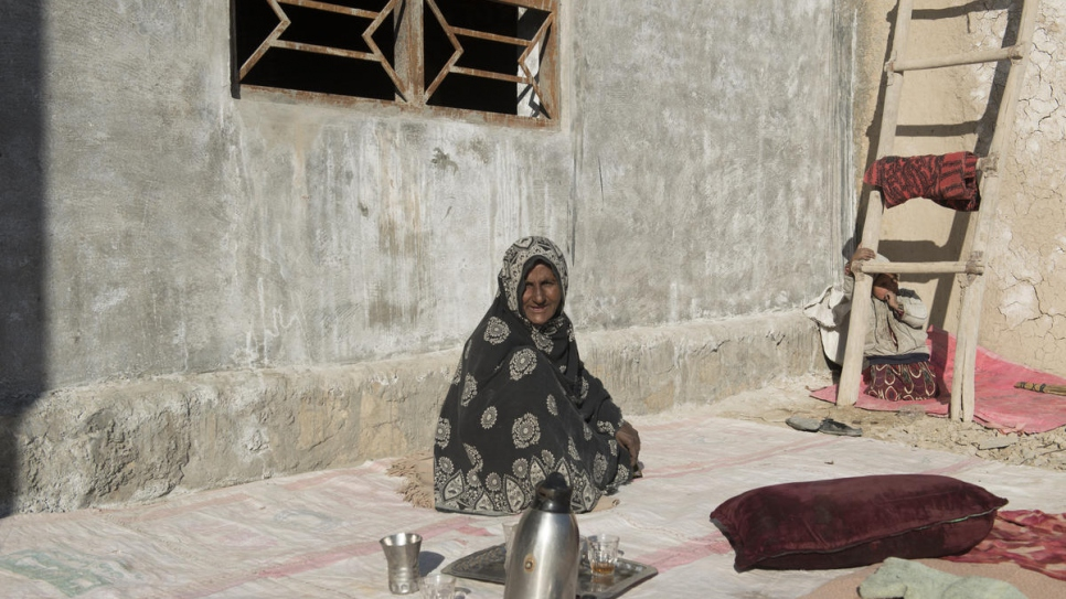 Sardar Bibi, 45, takes a tea break in front of her newly-built shelter in Kandahar province, on 4 February, 2020.