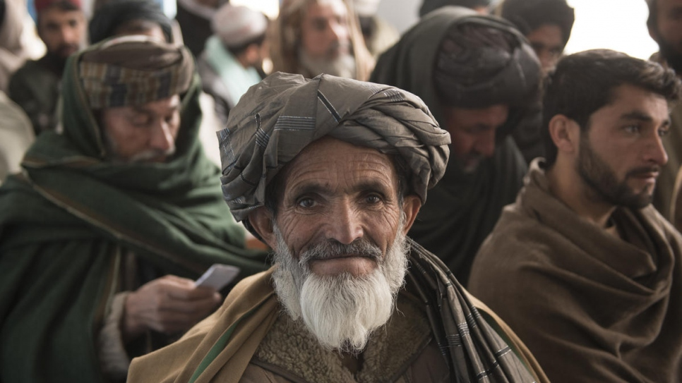 Mohammed Daud (centre) waits with other Afghan men in Kandahar City to receive the third installment of his cash grant from UNHCR to build a home for him and his family (2 February, 2020).