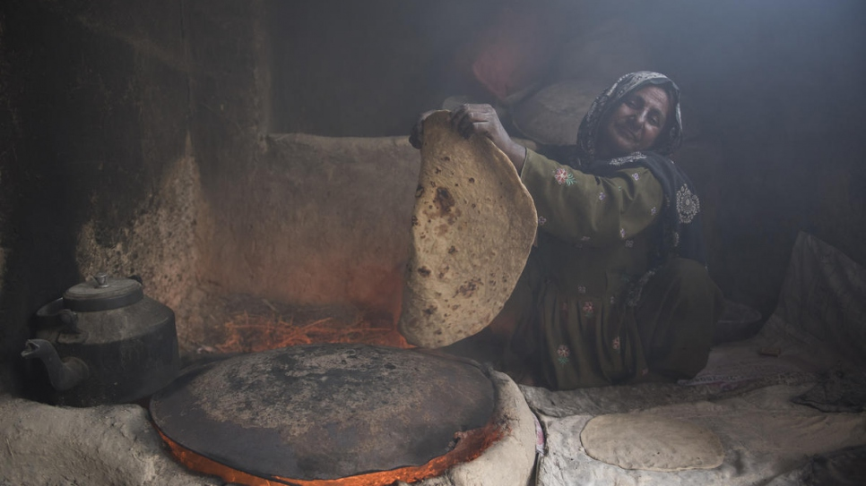 Sardar Bibi cooks traditional Afghan bread in the one-room shelter she shares with 21 members of her family. They will soon move into their new, larger home (4 February, 2020).