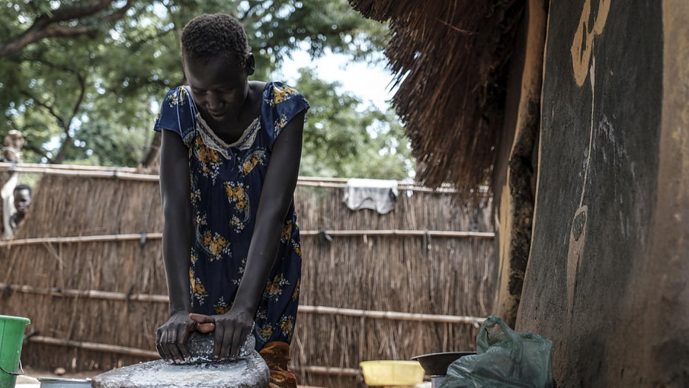 Nyamach Lul, 16, crushes kernels of maize into flour outside the house she shares with her 13-year-old sister in Jewi refugee camp, Ethiopia. Nyamach and her sister are unaccompanied minors.