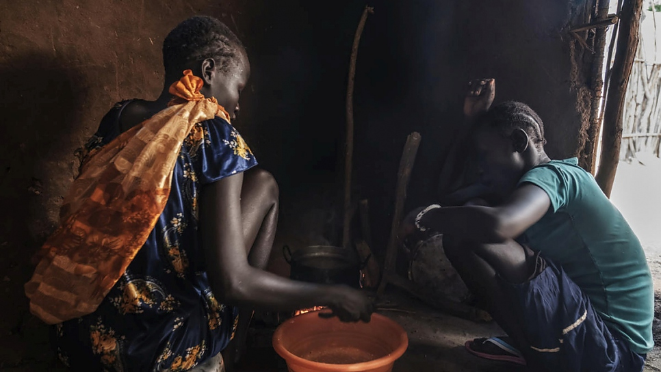 Unaccompanied South Sudanese minors, 16-year-old Nyamach Lul (left) and 13-year-old Nyakoang (right) prepare food at home in Jewi refugee camp, Ethiopia.