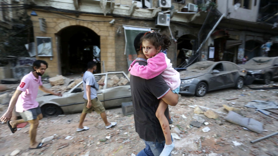 A man carries an injured child to safety following a massive blast in the port of Beirut, Lebanon.