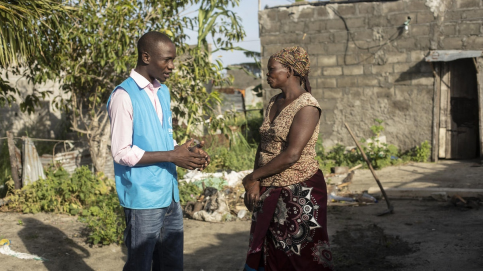 Luis Jose Faife speaks with a woman who survived cyclone Idai in Beira, Mozambique. The roof of her house, behind her, was blown away.