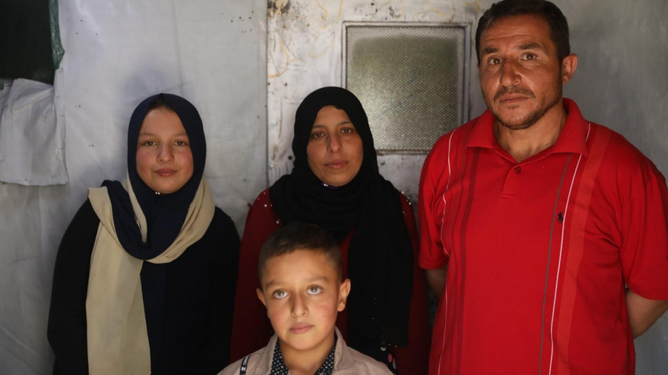 Khalil (right) with his family, including 12-year-old daughter Nahed (left) who dropped out of school to earn money picking vegetables.