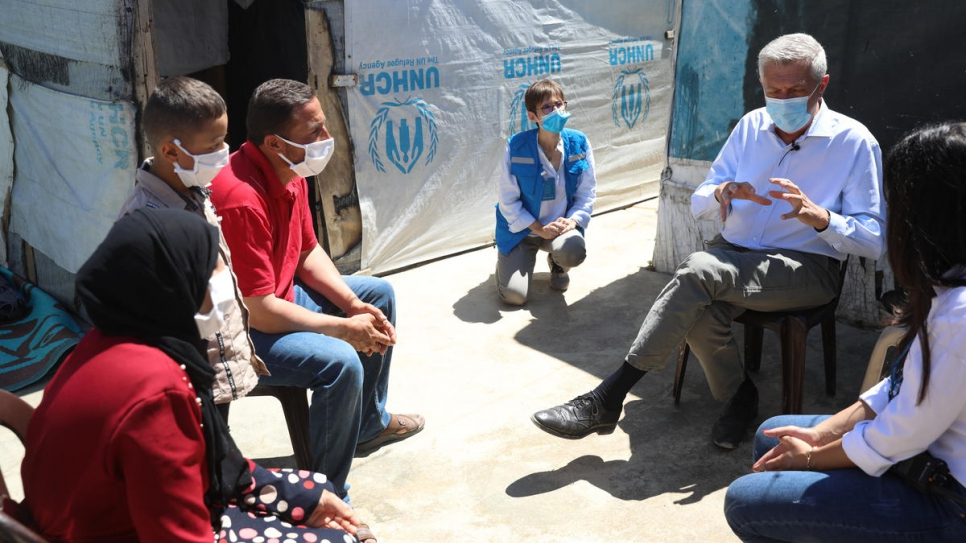 Grandi speaks with Khalil and his family outside their home in an informal tented settlement in Lebanon's Bekaa Valley.
