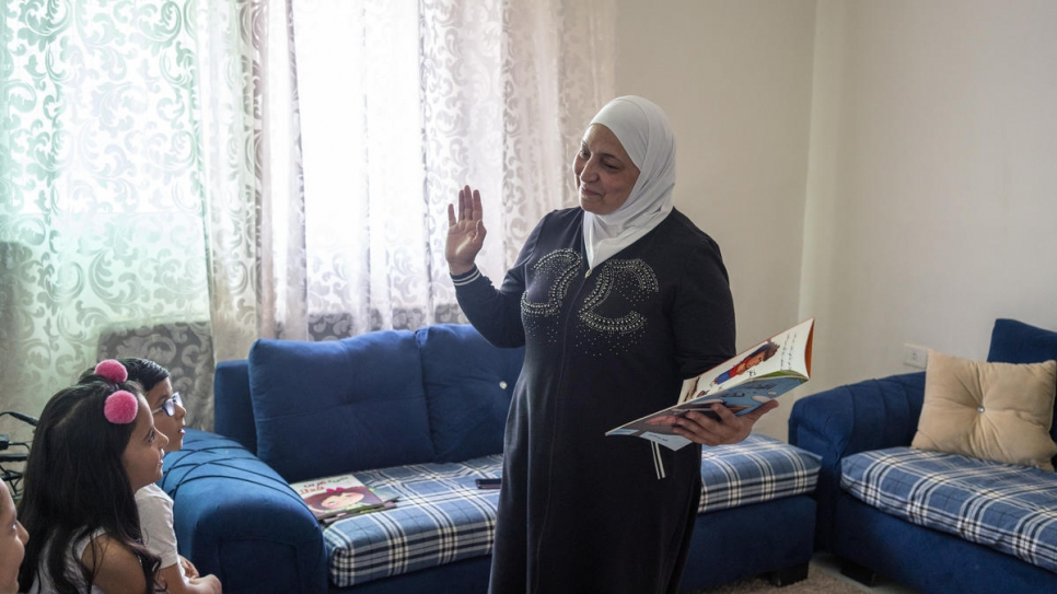 We Love Reading ambassador Latifa Al-Laham, 55, reads to a group of young fellow Syrian refugees in an apartment in Amman, Jordan.