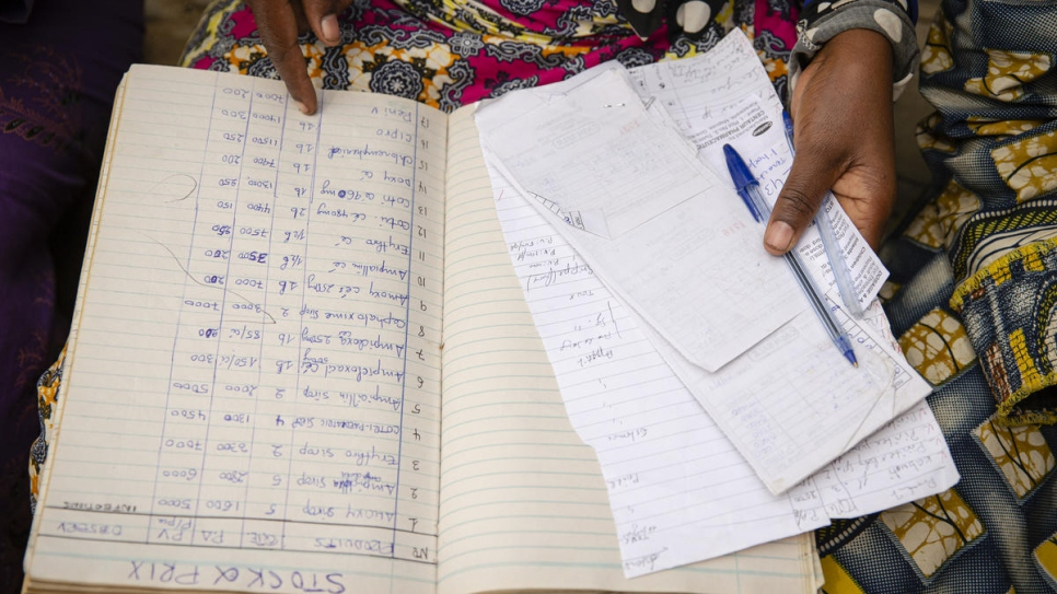 One of the refugee women mentored by Sabuni Francoise Chikunda goes over the records of the women's group founded in Nakivale settlement, Uganda.