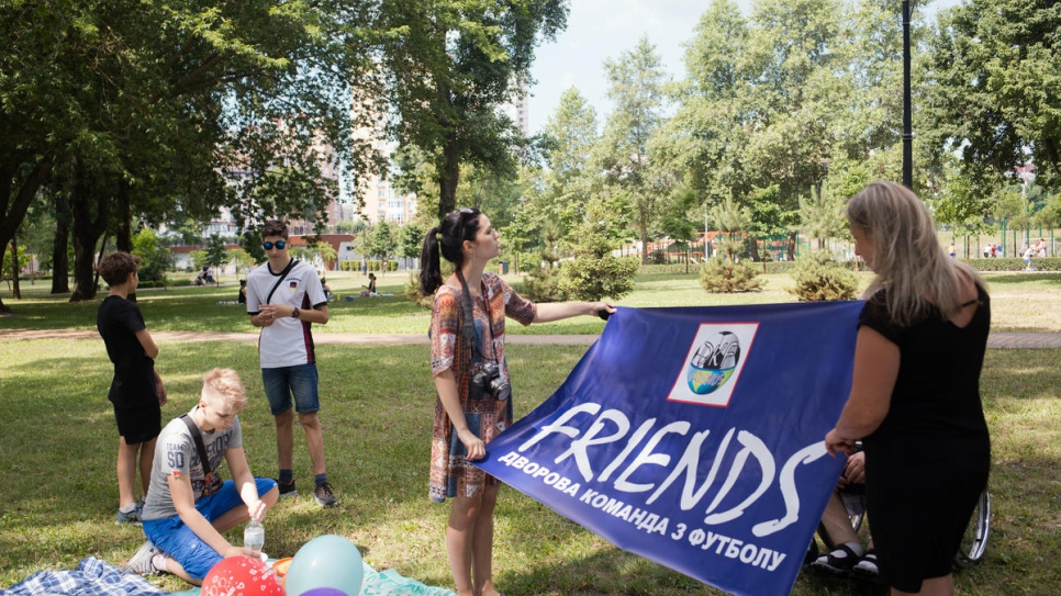 Valentyna Uvarova and Maryna Tolokova, who are internally displaced, hold a banner for Friends football team during a birthday party for Pavlo Soroka, son of Tetiana Baransova. The team fights discrimination in sports.