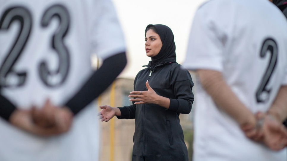 Rozma leads a football coaching session for girls.