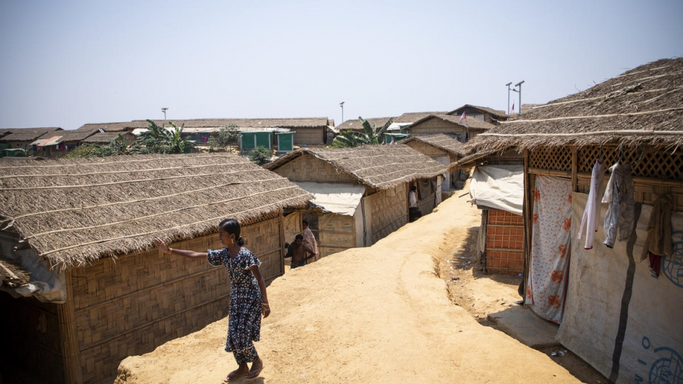 Myshara stands outside her family's home in Kutupalong camp.