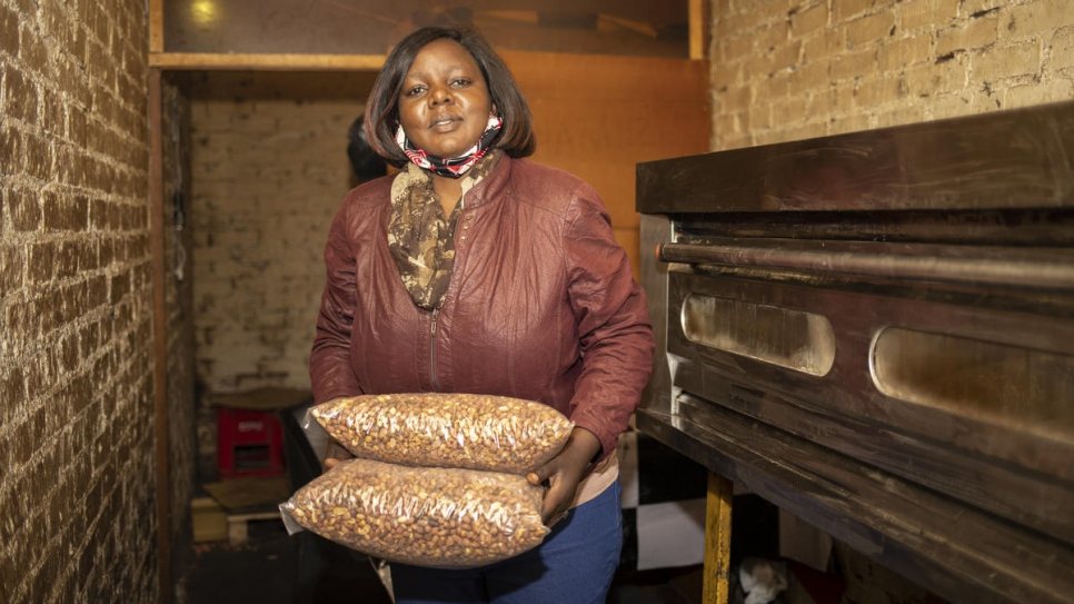 Congolese refugee Grace, 43, carries bags of roasted peanuts at her business in Pretoria, South Africa.