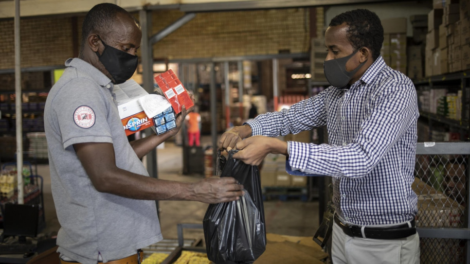 Amin Sheikh (right) hands a bag of items to a vulnerable South African during a food distribution in Pretoria, South Africa.