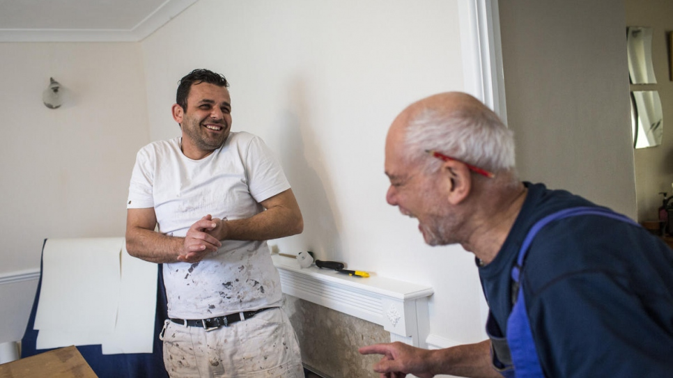 Hani Arnout (left), 34, shares a joke with local painter and decorator Trevor Leahong as they paint a house together in Ottery St Mary, Devon. Trevor gives Hani work whenever he can.