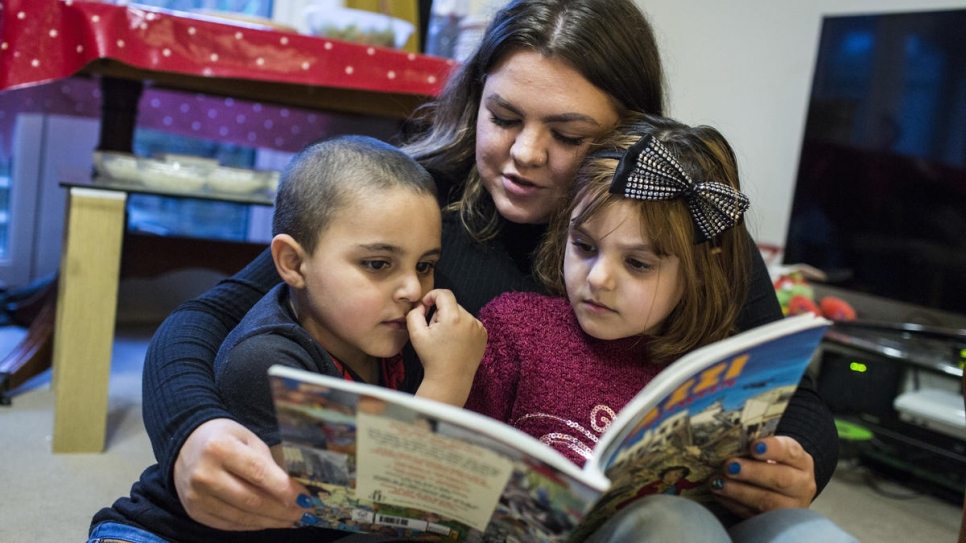 Amy Chapman reads with Adbul, 4, and Noor, 6, at the Arnout family home in Ottery St Mary, Devon, south-west England. Amy is a friend of the family and often drops by to help the children read English.