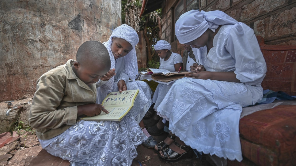 Nosizi Reuben (second from left), assists her sisters with their studies, outside their home in Kinoo, Kenya.