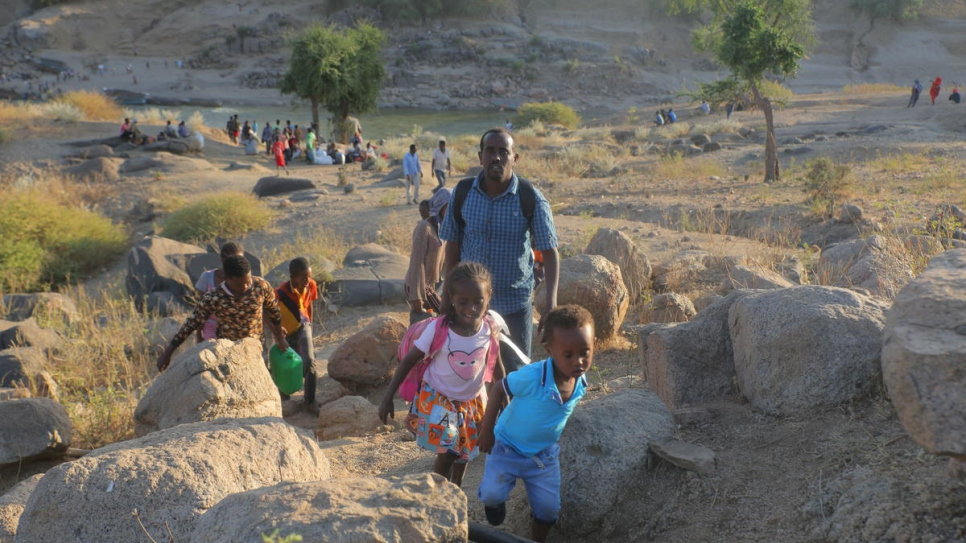 Ethiopian refugees walk through rocky terrain to reach Hamdayet, Sudan.
