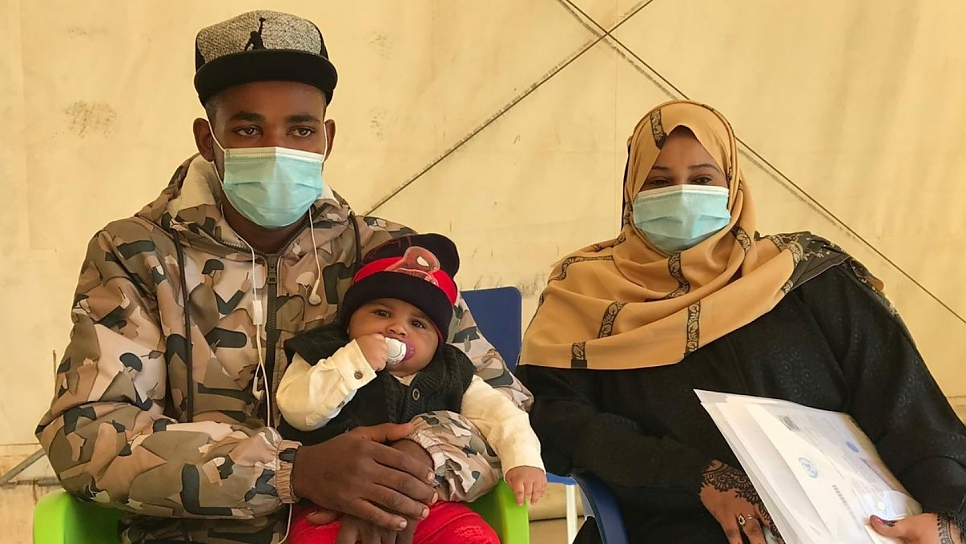 Somali asylum seekers Fawaz 21, Adnan, four  months, and Farah, 24, prepare to take the humanitarian evacuation flight from Libya to Rwanda.