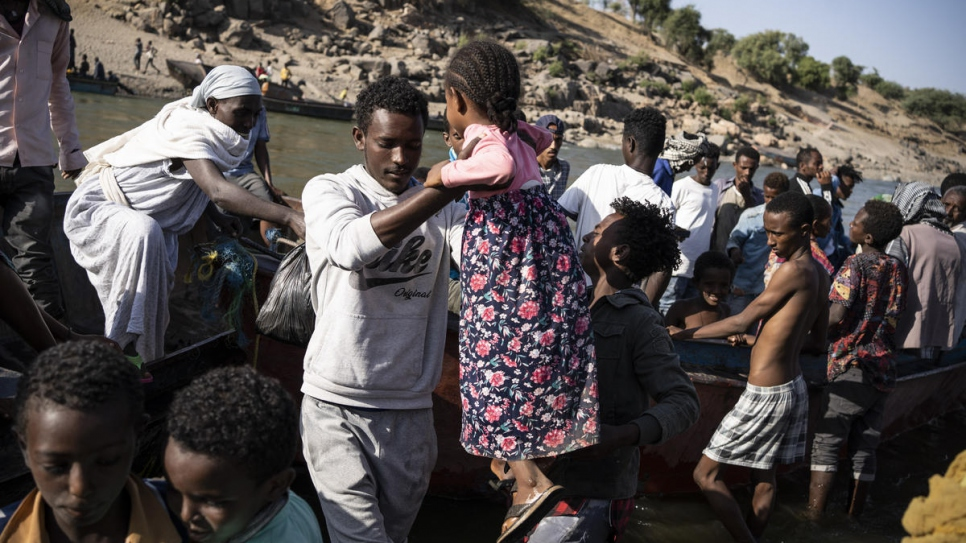 A young girl is lifted off a boat ferrying Ethiopian refugees across the Serit river, along the Hamdayet border point in Sudan.