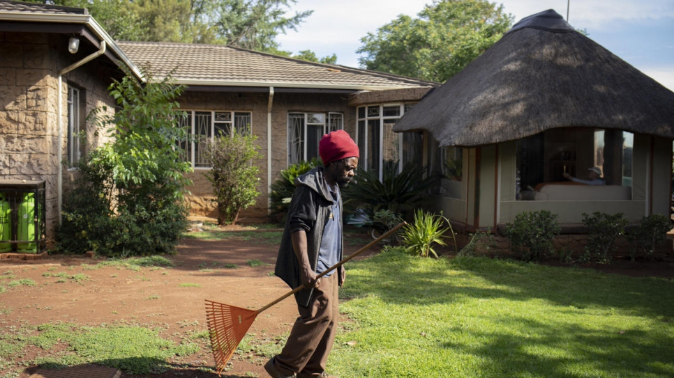 Raphael Chauke walks across the compound where he works as a gardener in Pretoria, South Africa.