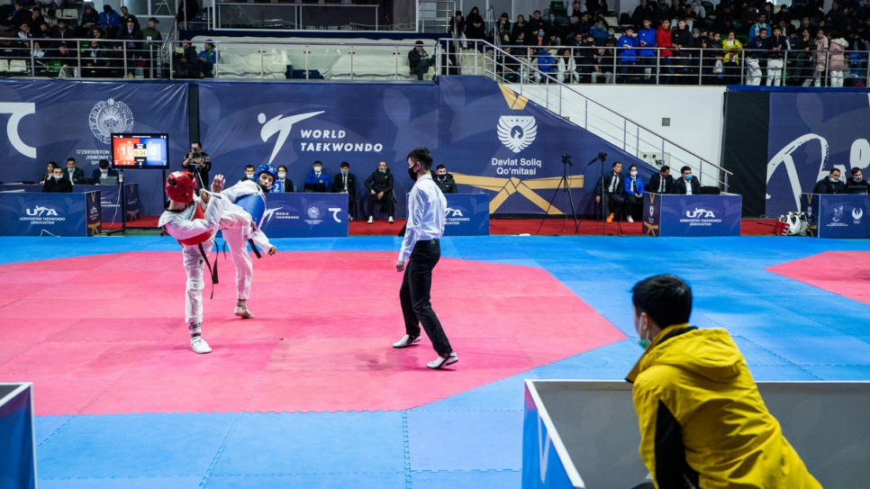 Mukhamadjon watches one of his students compete at the Taekwondo Federation.