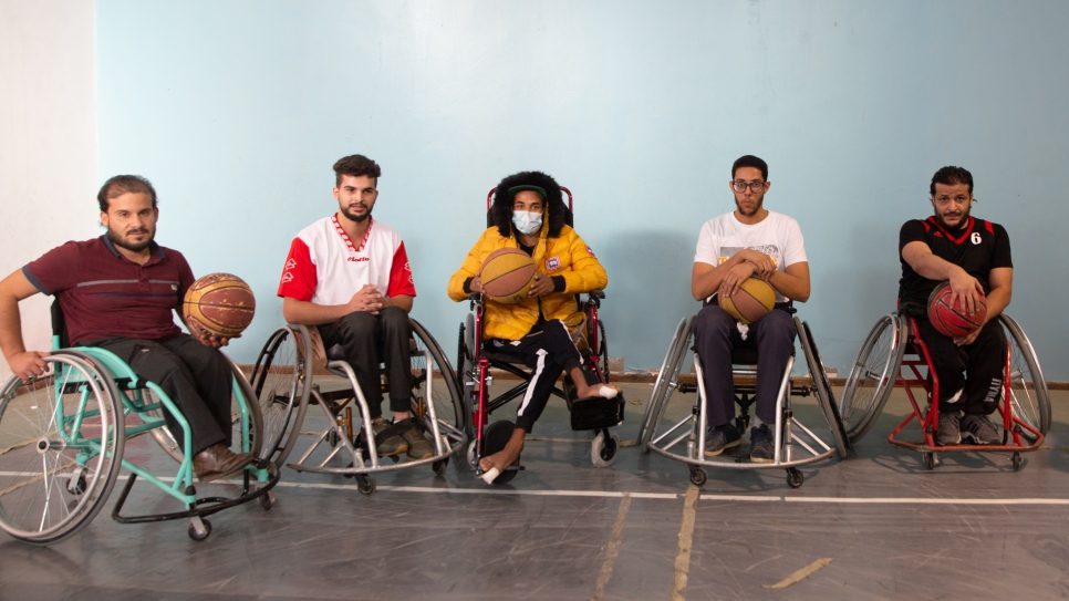 Mohamed (in yellow) has his photograph taken with other wheelchair users after watching them play a game of basketball.