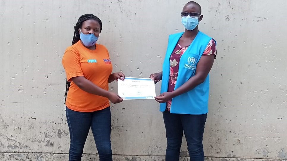 Lynette Lagat (right), UNHCR's Associate Protection Officer on Statelessness, presents a completion certificate to Diana Mbiti, one of the participants of the online statelessness course.