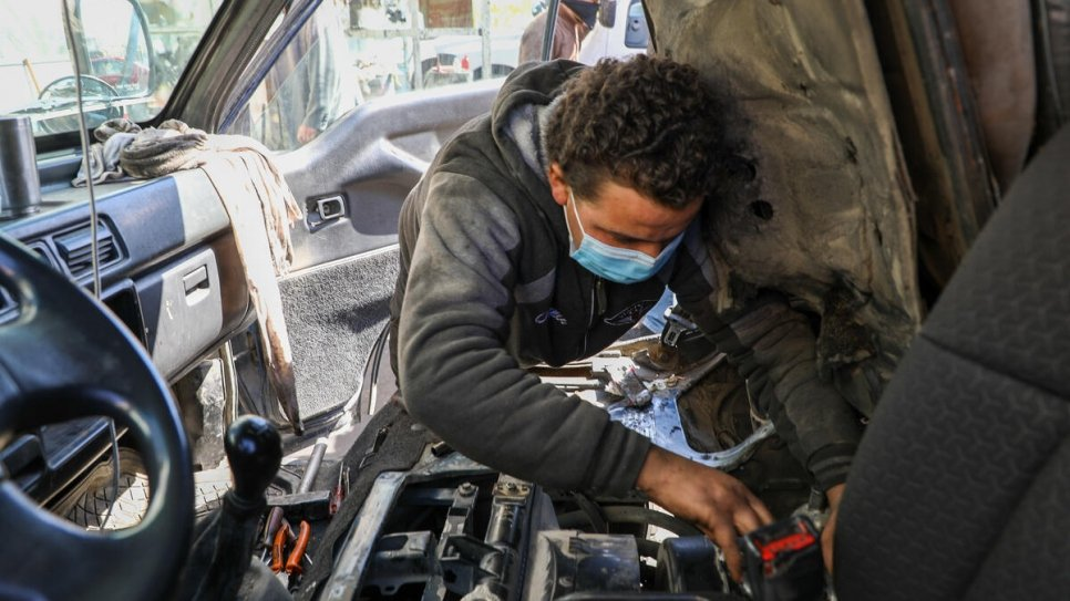 Syrian refugee Khalil, 18, repairs a vehicle at the garage in Amman where he works for US$10 each day.