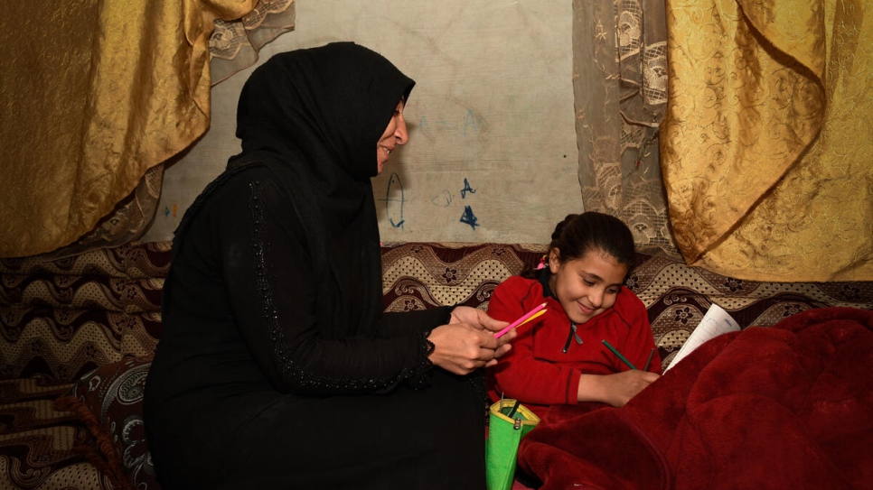 Amal's mother Samar, 37, sits with her daughter, who lost a leg in an explosion aged 18-months.