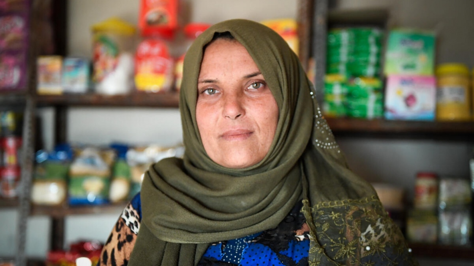 Abeer stands in the mini market she opened with the help of a small business grant funded by UNHCR.