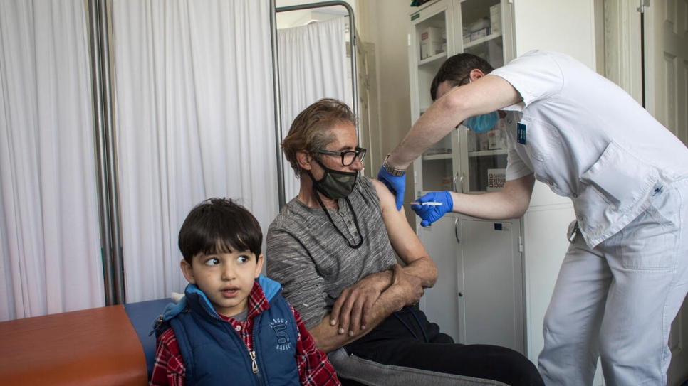 A resident of an asylum centre outside Belgrade receives a jab of coronavirus vaccine.