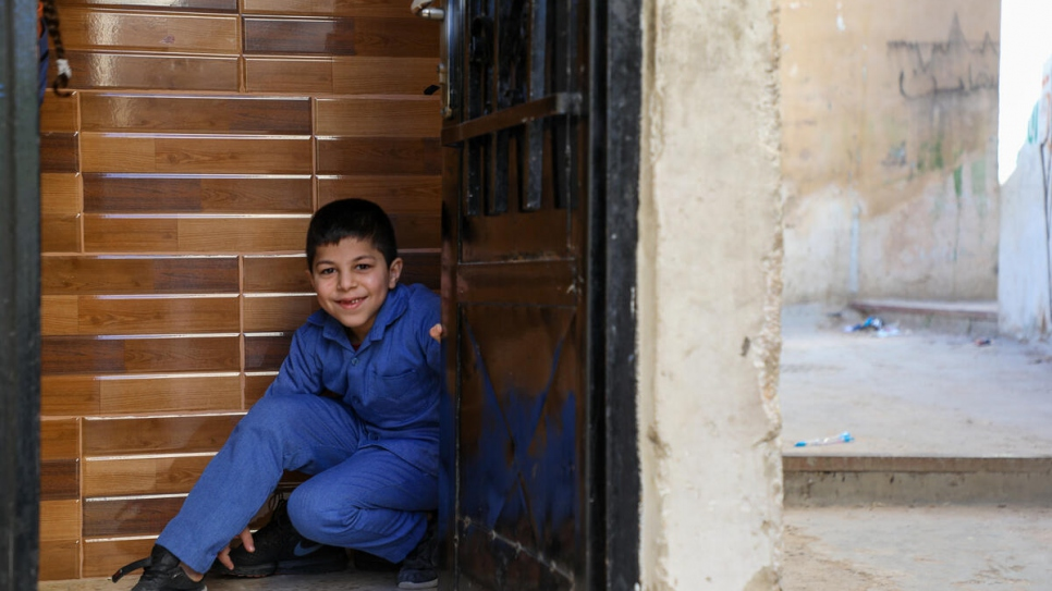 Jameela's youngest son Ahmed, 8, in the doorway of their apartment in Amman, Jordan.