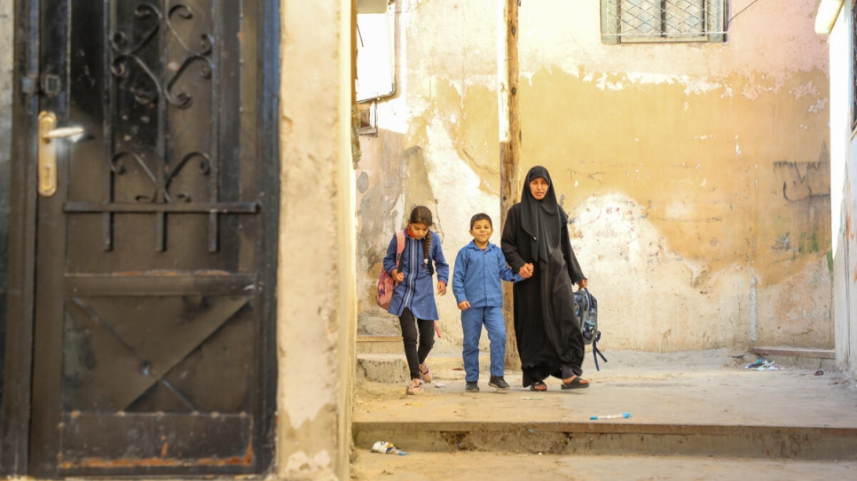 Aisha, 10, and Ahmed, 8, walk home with their aunt Huda before the recent closure of schools due to COVID-19.