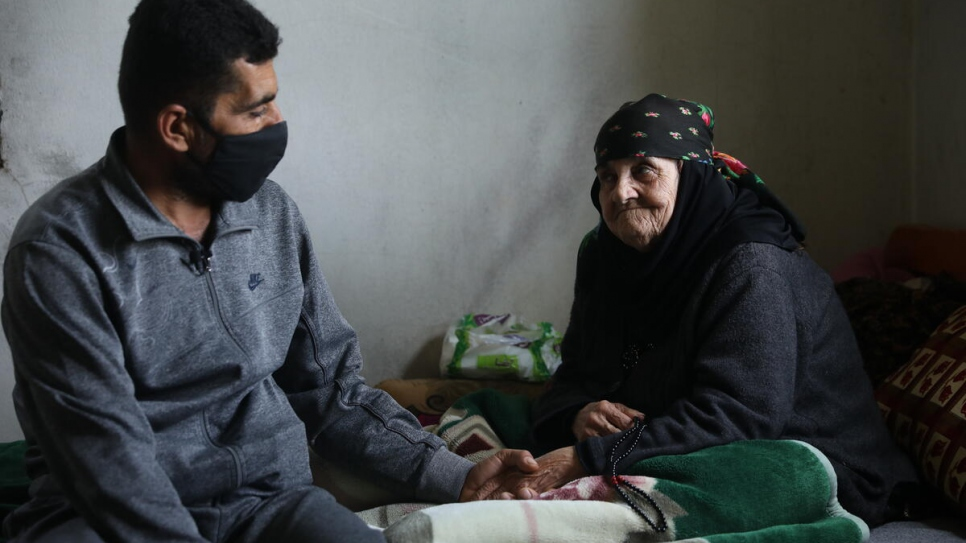 Amina, 85, sits on the bed with her son Abdo at the home they share in Touline, Lebanon.