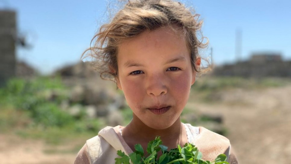 A young girl carries a bunch of coriander outside her damaged home in a village near Mosul.