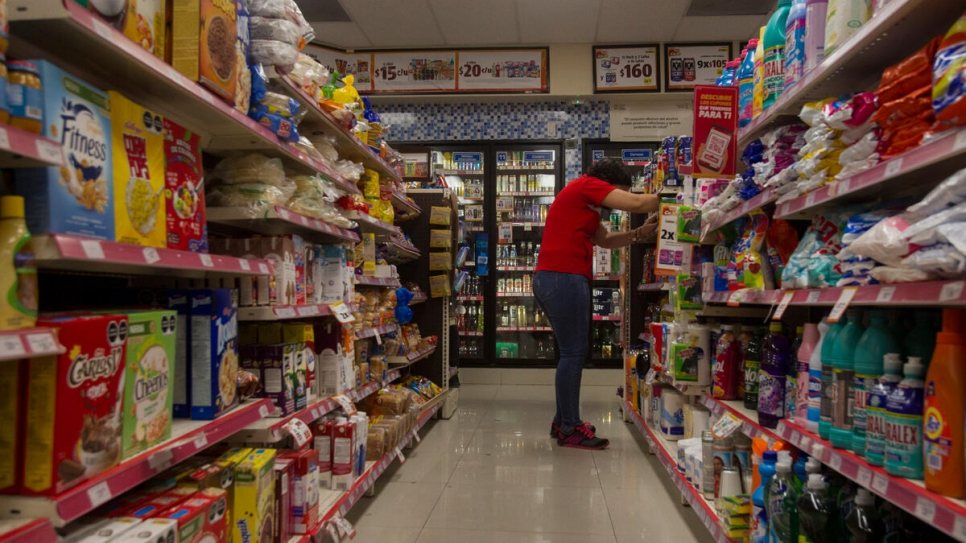 A Salvadoran refugee stacks shelves at a convenience store in Monterrey, Mexico, where she works as a shift supervisor.