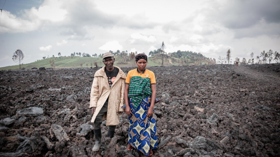 Jean and Esperance Muhoza stand on volcanic rock that now covers their former home, which was destroyed in the eruption.