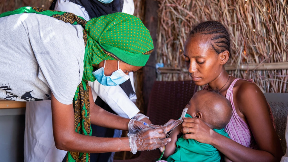 Ethiopian refugee Mihret, 25, takes details of a child at the clinic where she volunteers in Tunaydbah settlement, Sudan.