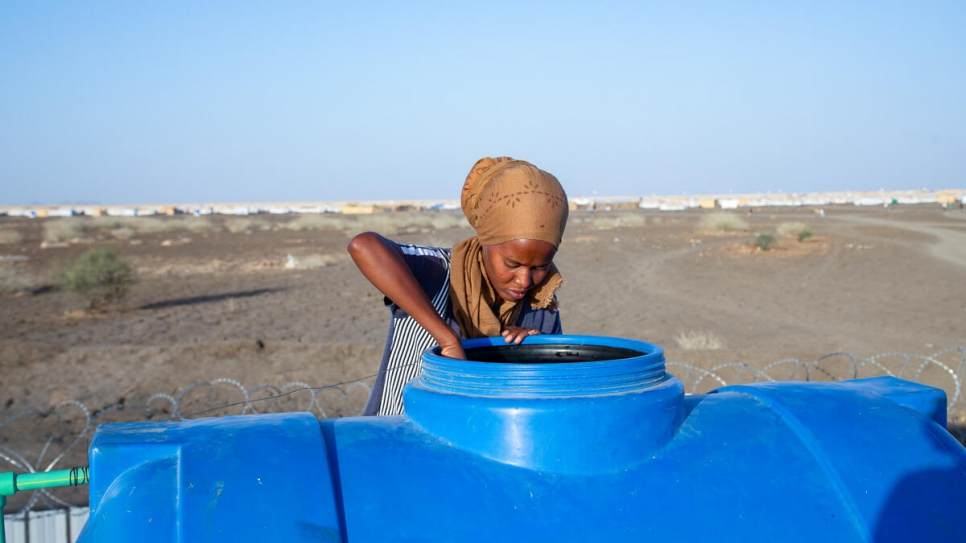 Mihret, an Ethiopian refugee and engineer, checks the water level in a tank set up at the mobile office base in Tunaydbah settlement, Sudan.