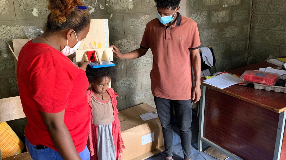 Brukti* a displaced Ethiopian nurse, checks the height of a child at a makeshift clinic in Mekelle, Ethiopia.
