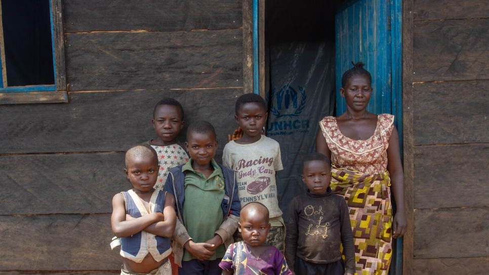 Elodie, a displaced Congolese woman stands with her children outside their durable shelter in Beni, in north-eastern Democratic Republic of the Congo.