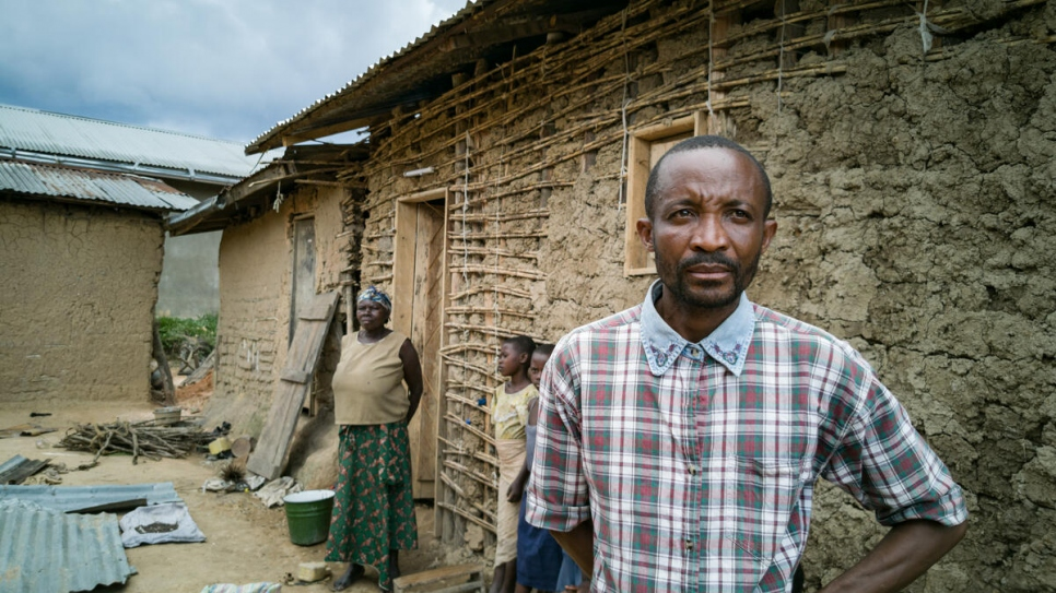 Evan Sikiani, a displaced Congolese man, stands outside the compound of his host, Kahambu Mwavuli (back), where up to 25 people live in Beni, in north-eastern Democratic Republic of the Congo.