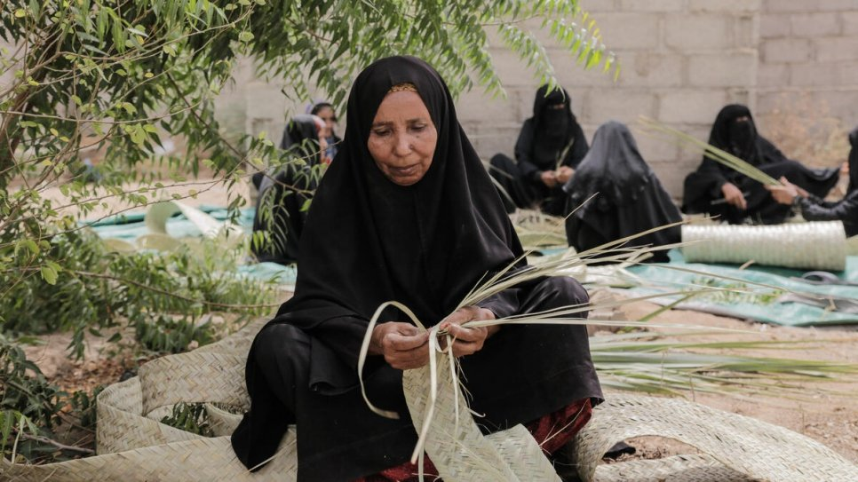 Yemeni women at a displacement site near Hudaydah weave khazaf palm fronds used in the construction of environmentally sustainable shelters.