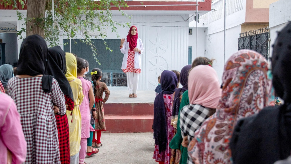 Addressing an assembly at her former school, Saleema encourages the young refugee girls to keep studying and following their dreams.