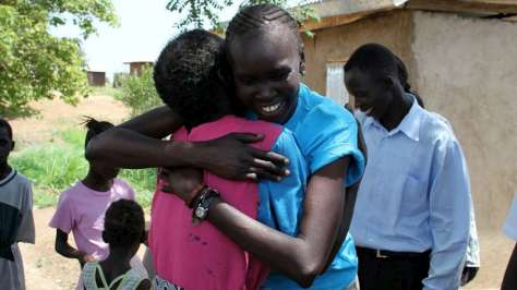 Supermodel, former refugee and UNHCR Refugee Advocate, Alek Wek greets a woman in a returnee community in Juba, South Sudan. UNHCR/B.Sokol/July 9, 2012