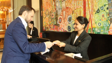Tajikistan. Afghan refugee Nargis, confidently receiving a guest at the Front Desk, during the Apprenticeship Programme at the renown Sheraton Hotel in Dushanbe