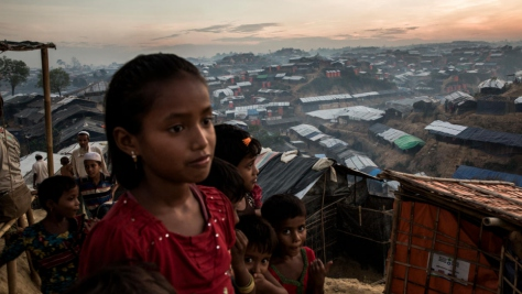 Young Rohingya refugees on a hillside at dusk overlooking a sprawling array of shelters.