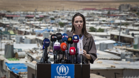 Angelina Jolie stands at a podium covered with news microphones, with Domiz refugee camp in the background